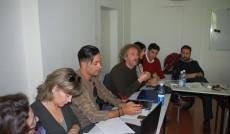 Partnerzy w projekcie Kiitos podczas spotkania - siedzą przy stołach ustawionych w podkowę