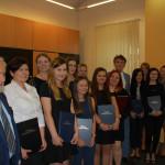 Grupa studentek oraz członkowie komisji egzaminacyjnej na wspólnym zdjęciu