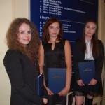Trzy studentki pozują z pracami na korytarzu przed tablicą informacyjną