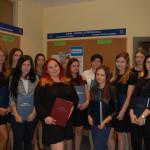 Grupa studentów pozuje z pracami dyplomowymi