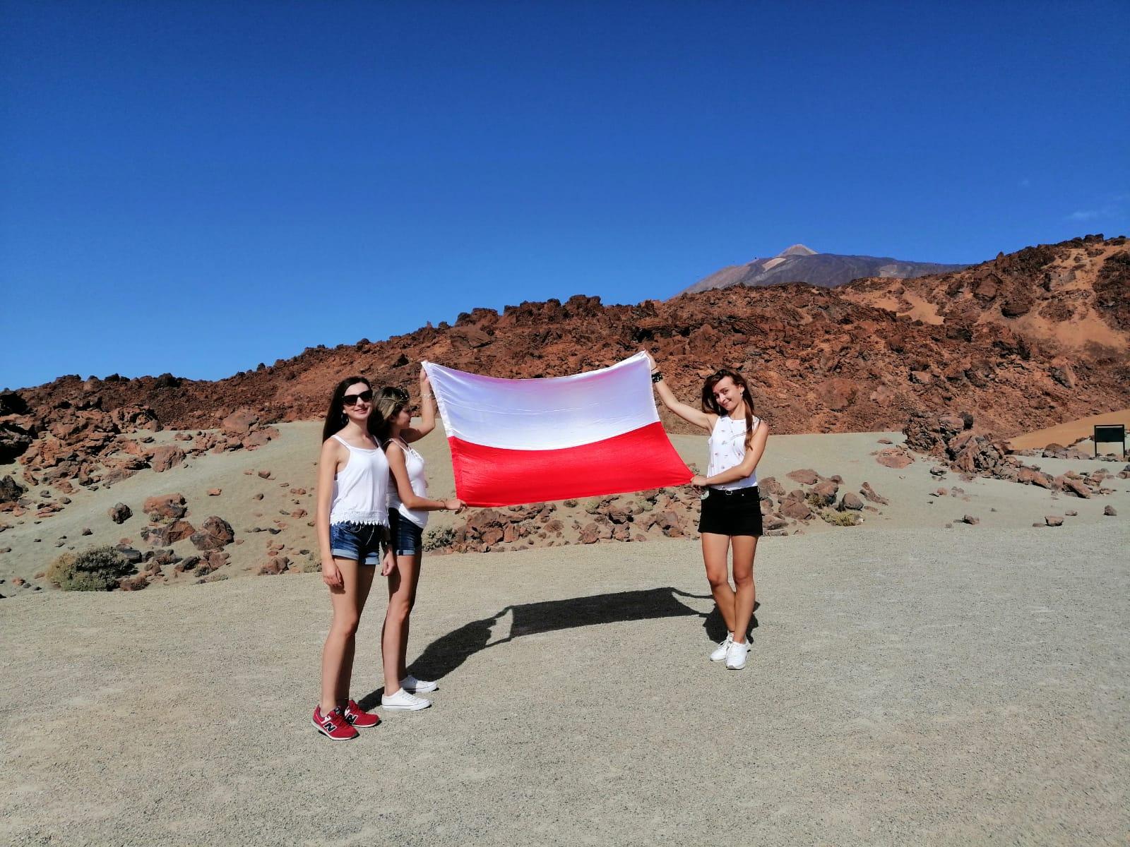 Trzy studentki trzymające rozłożoną polską flagę, w tle skały