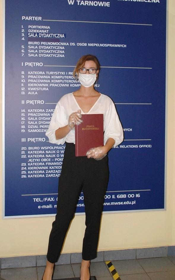 Studentka pozuje z pracą dyplomową na tle tablicy informacyjnej