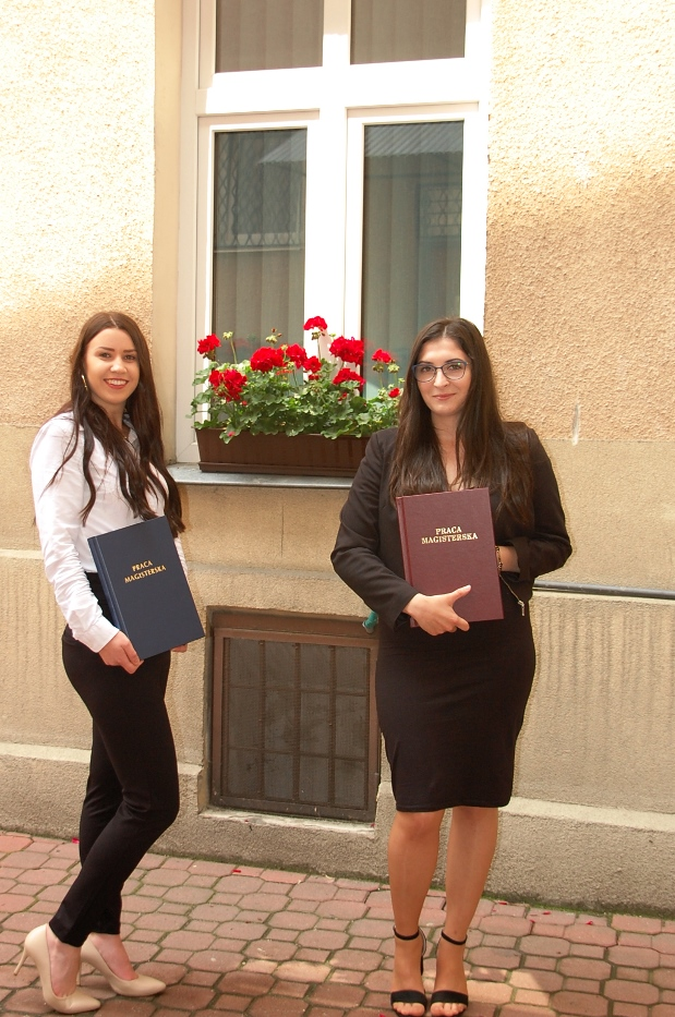 Dwie studentki z pracami dyplomowymi na dziedzińcu budynku przy ul. Szerokiej 9