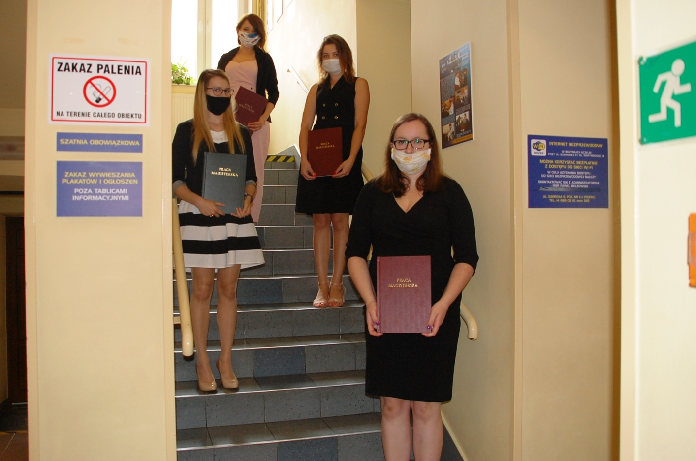 Studentki pozują z pracami dyplomowymi na schodach budynku przy ul. Szerokiej 9
