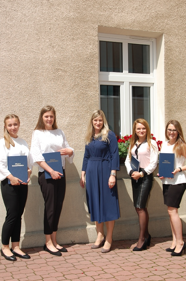 Grupa studentek po egzaminie dyplomowych na dziedzińcu budynku MWSE