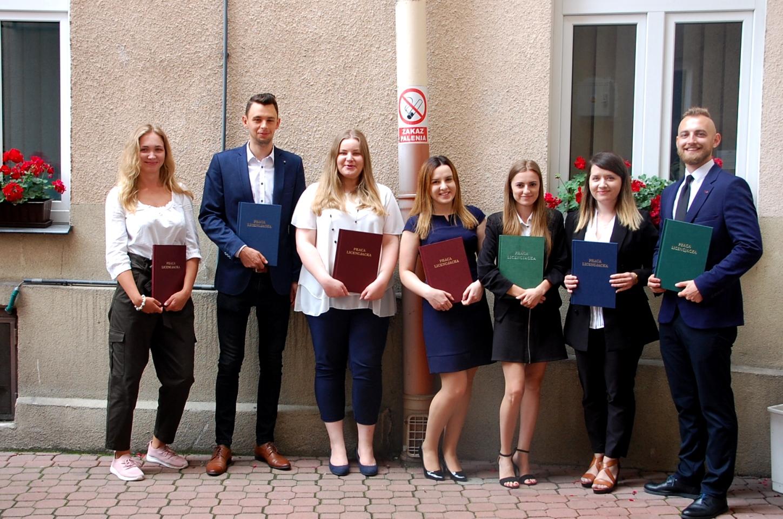 Grupa studentów pozuje z pracami dyplomowymi na dziedzińcu budynku przy Szerokiej 9