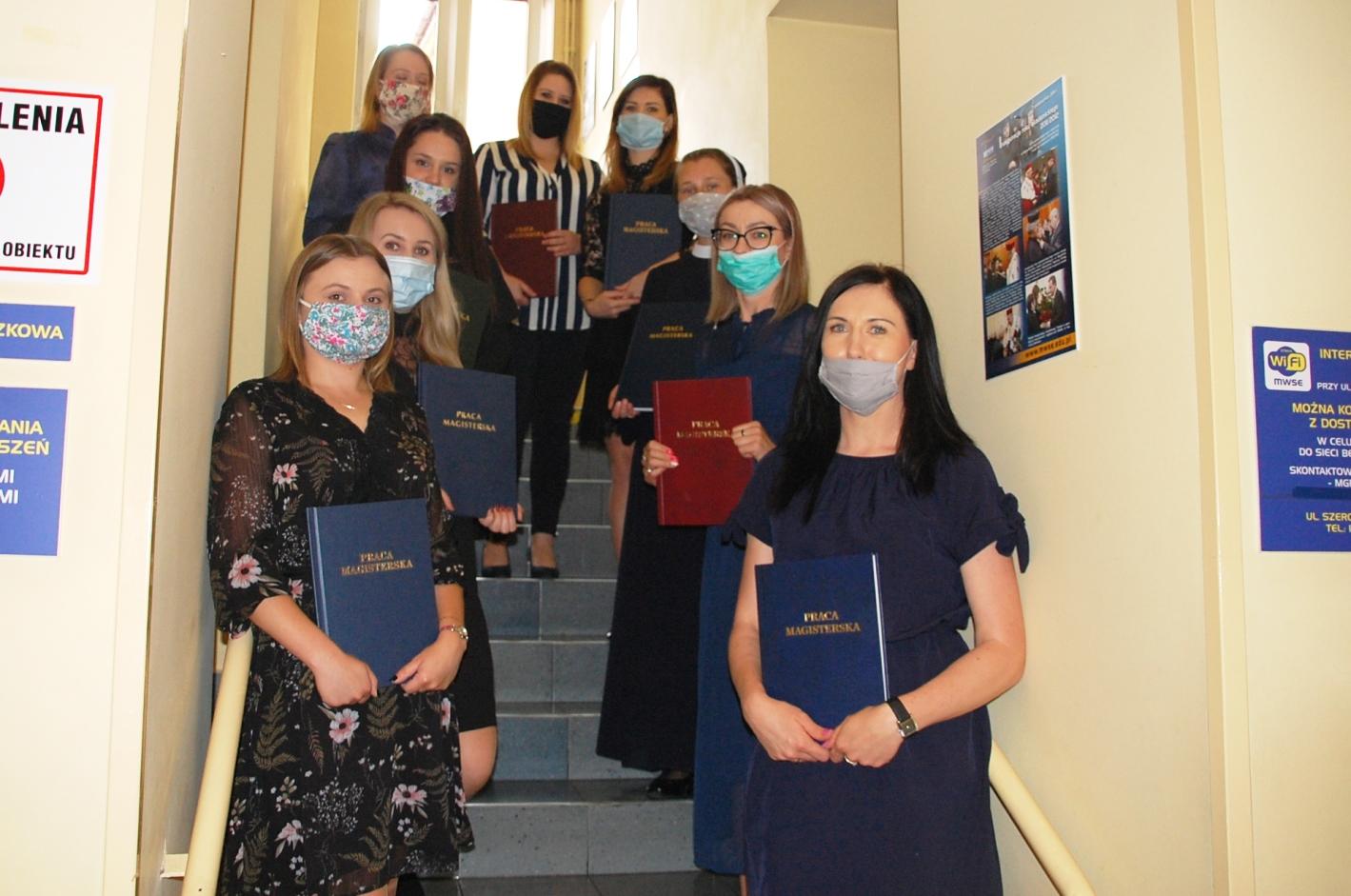 Grupa studentów pozuje z pracami dyplomowymi na schodach budynku przy Szerokiej 9