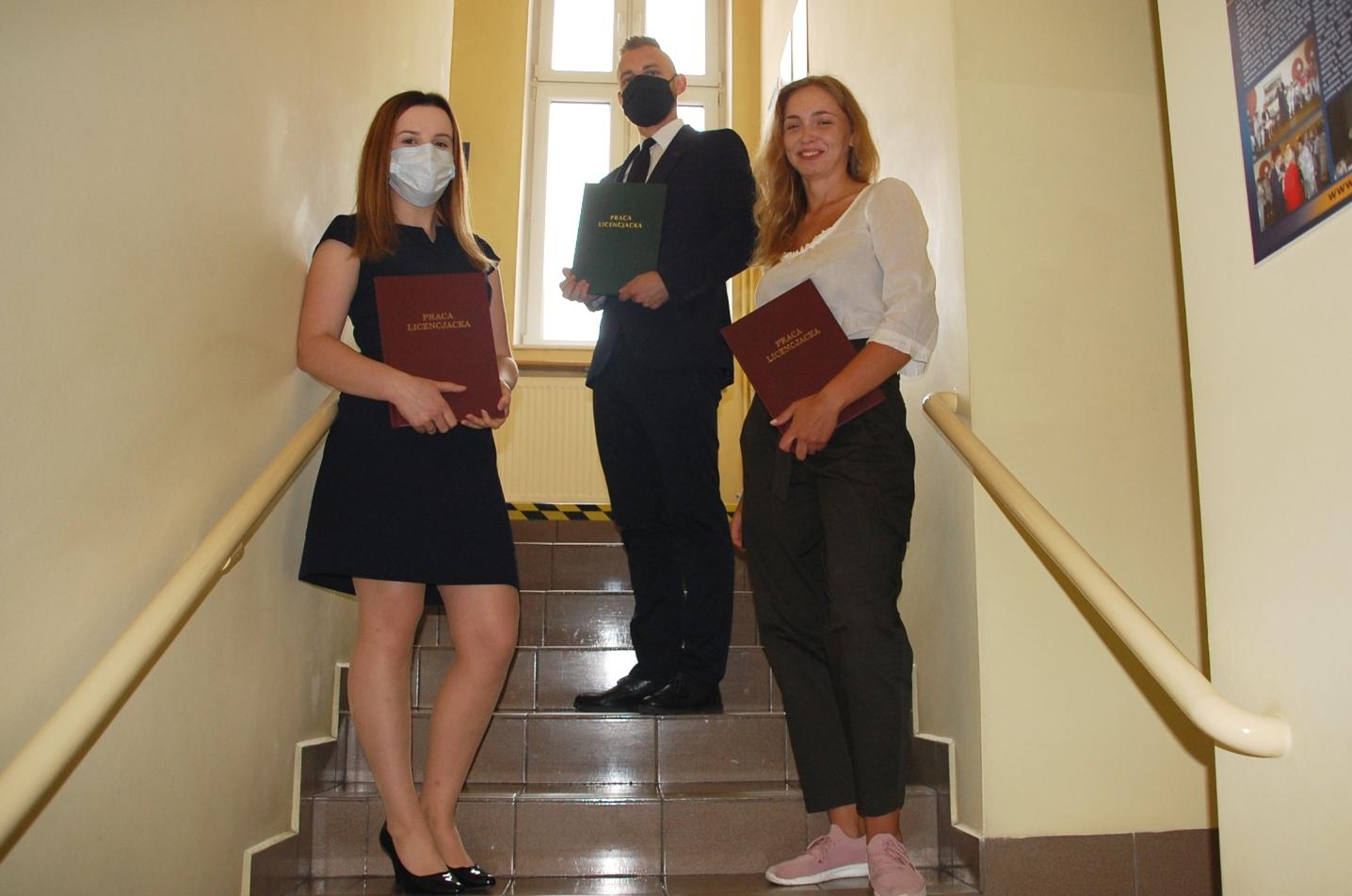 Troje studentów pozuje z pracami dyplomowymi na schodach budynku przy Szerokiej 9
