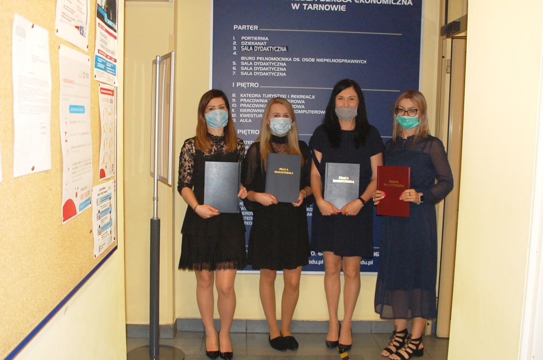 Cztery studentki z pracami dyplomowymi przed tablicą informacyjną przy Szerokiej 9