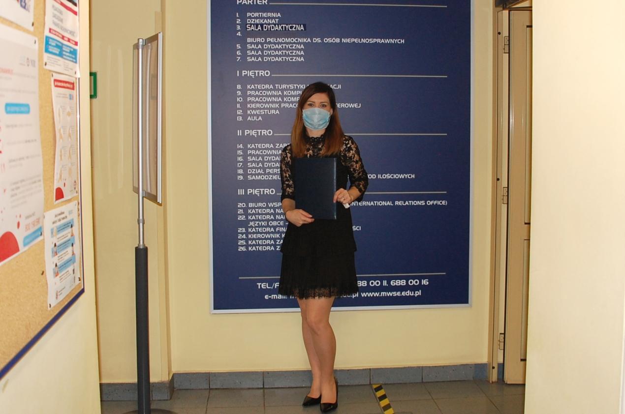 Studentka przed tablicą informacyjną w budynku przy ul. Szerokiej 9