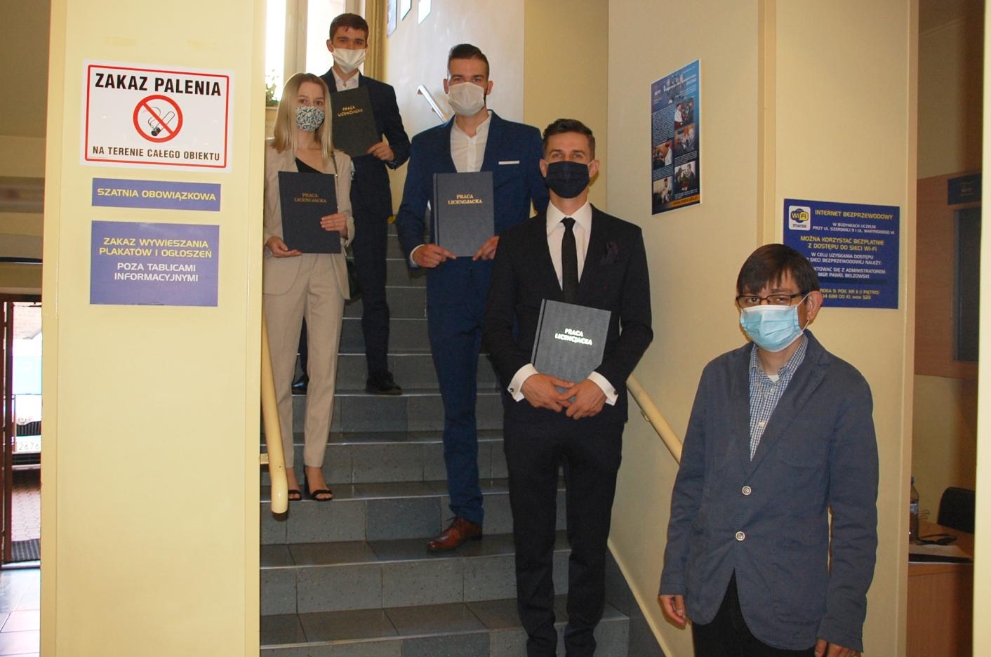 Czworo studentów na schodach budynku przy Szerokiej 9, z prawej stoi dr Michał Kozioł - promotor