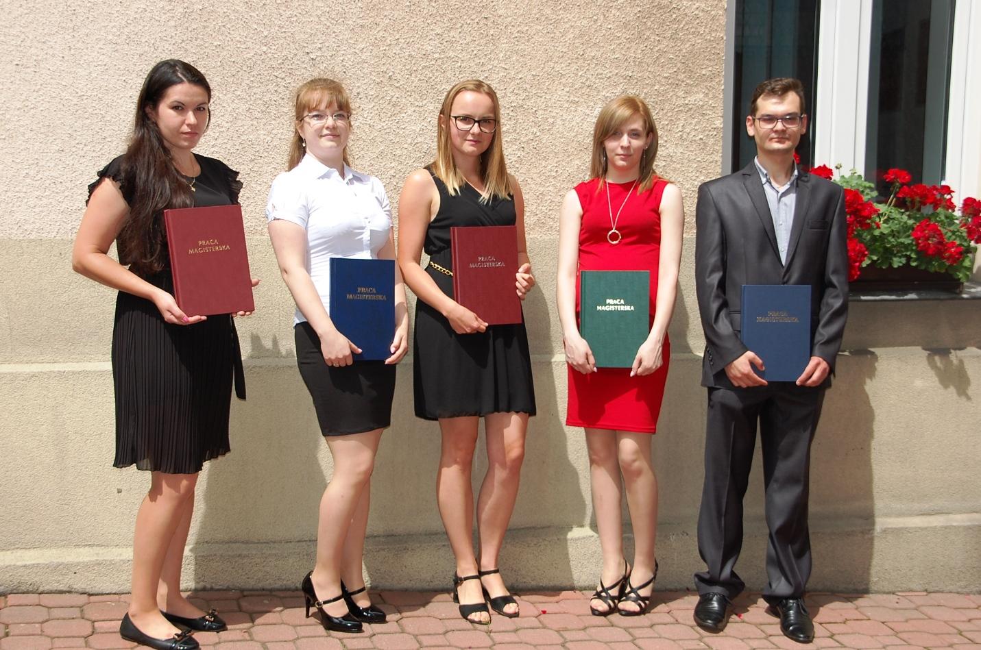 Pięcioro studentów pozuje z pracami dyplomowymi na dziedzińcu budynku przy Szerokiej 9